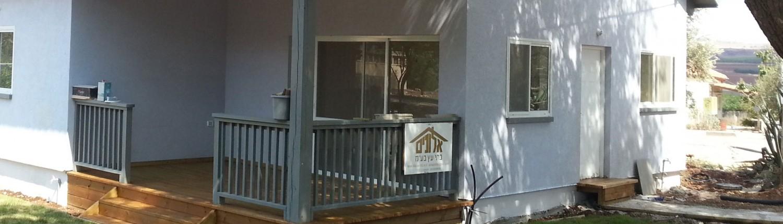 בית מעץ בצבע אפור עם דק, קבלן מבצע אלונים בתי עץ